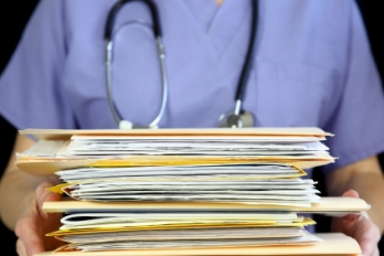 doctor holding stack of files and papers